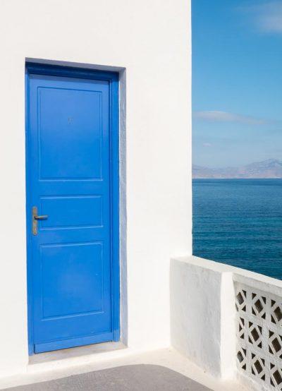 foto di viaggio in grecia con una porta blu che si apre sul mare