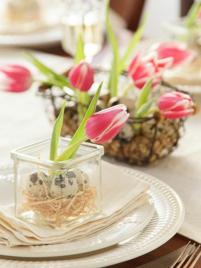 Foto di tavola imbandita con decorazioni pasquali con tulipani e Uova di quaglia